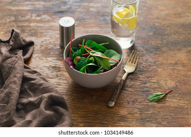 Bowl of salad with spinach leaves and beet leaves on dark wooden table with glass of water with lemon. Vegetarian biodynamic food concept