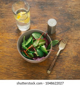 Bowl of salad with spinach leaves and beet leaves on dark wooden table with glass of water with lemon. Top view. Vegetarian biodynamic food concept
