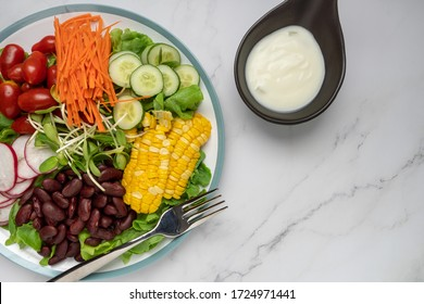 bowl of salad with vegetables ,fresh green oak salad, tomatoes, corn, Red beans, Carrot , red radish, olive oil and cucumber on white marble table. Top view. Food Concept for healthy diet