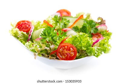 bowl of salad with vegetables and greens on white background