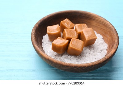 Bowl with salt and caramel candies on color wooden background