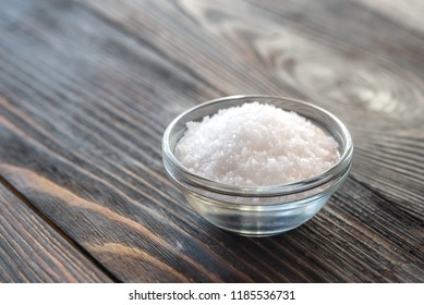 Bowl of salt on the wooden background