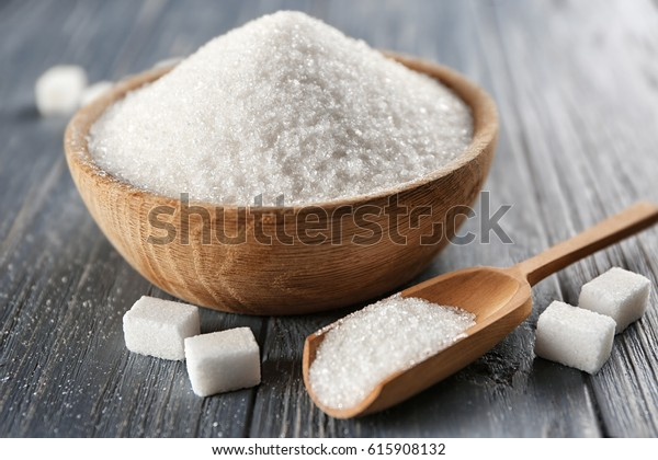 Bowl and scoop with white sand and lump sugar on wooden background