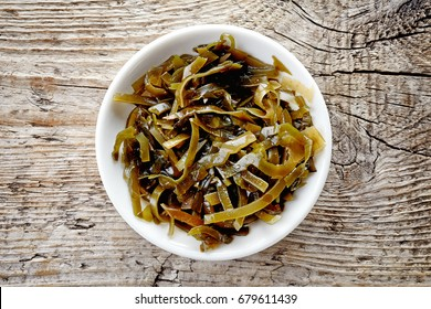 Bowl of sea kale on wooden background, top view