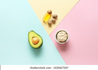 Bowl with shea butter, essential oil and avocado on color background