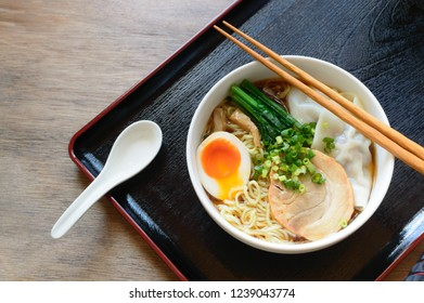 a bowl of shoyu (soy sauce) ramen topped with soft boiled egg, spinach, grilled pork, wonton and spring onion