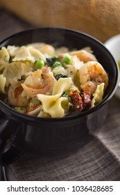 Bowl of shrimp farfalle alfredo with peas spinach and sundried tomatoes