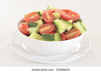 A bowl of sliced baby plum tomatoes and cucumber
