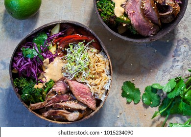 Bowl with sliced beef steak, broccoli, red cabbage, broccolli sprouts and satay sauce