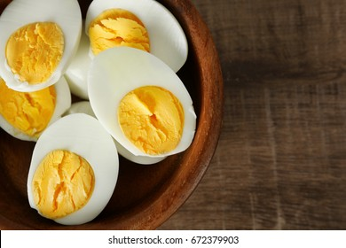 Bowl with sliced hard boiled eggs on wooden table. Nutrition concept