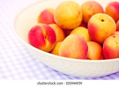 a bowl of some fresh apricots on summer tablecloth