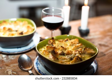 A bowl of soup with cheese and bred crumbs, with a glass of whine and candles