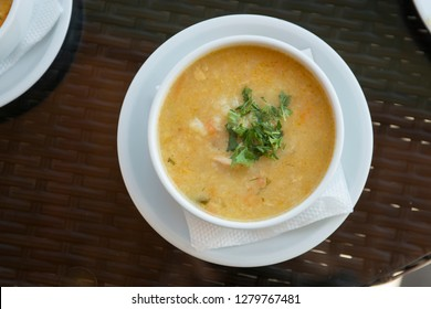 A bowl of soup with chicken and vegetables on the table in the restaurant