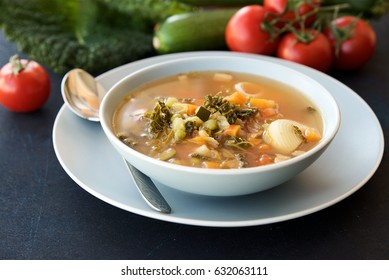 Bowl of soup Minestrone. Dark blue structural background. Italian Cuisine