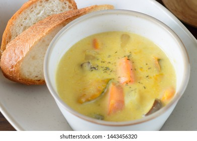 a bowl of soy mike chowder accompanied with French baguette on wooden background