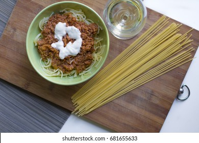 A bowl of spaghetti bolognese with some sour-cream and a glass of white wine