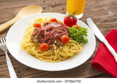 Bowl of spaghetti bolognese with tomatoes on wooden table in background