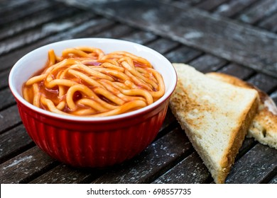 Bowl of Spaghetti in Tomato Sauce Against a Dark Weathered Table Top