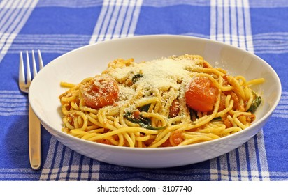 A bowl and spaghetti and tomato sauce with pecorino cheese on a blue striped tablecloth