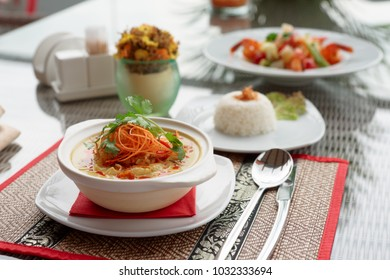 Bowl of spicy curry dish with coconut milk on restaurant table outdoors