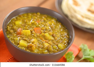 Bowl of spicy Indian dal (lentil) curry prepared with carrot and potato, chapati flat-bread in the back and cilantro leaf on the side (Selective Focus, Focus one third into the curry)