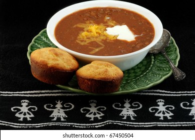 Bowl of spicy Tex-Mex chili and jalapeno cornbread with melted cheese and dollop of sour cream on black place mat with Aztec design.