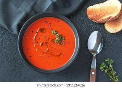 Bowl of spicy tomato soup garnished with splash of olive oil and black pepper