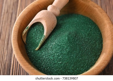 Bowl with spirulina powder and scoop on wooden background