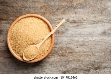 Bowl and spoon with brown sugar on wooden background