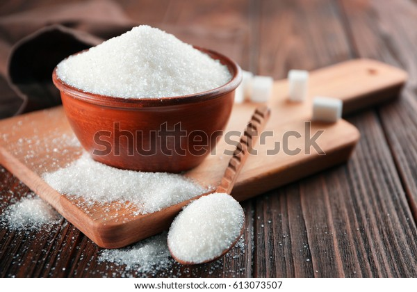 Bowl and spoon full of sugar on wooden background
