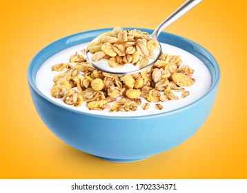 Bowl and spoon with oat granola, milk, yogurt on orange background. With clipping path.