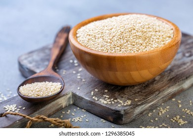 Bowl and spoon with sesame seeds on wooden serving board, selective focus.