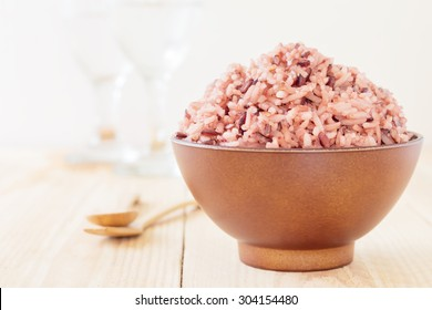 Bowl of steamed brown rice on wood table