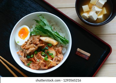 a bowl of stir fried  pork with kimchee on steamed rice
