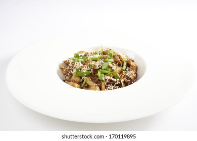 Bowl of stir fried udon noodles with mushrooms garnished with sesame seeds