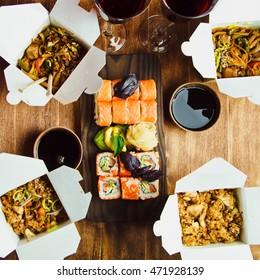 Bowl of stir fried udon noodles garnished with black sesame seeds and fresh mint with wooden chopsticks, sushi and glasses wine. Dinner s Japanese restaurant