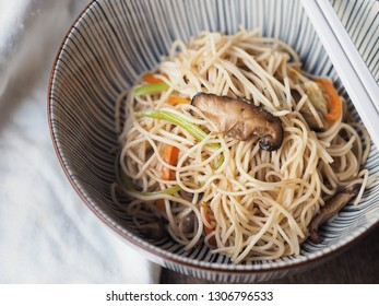 Bowl of stir-fried Chinese noodles with vegetable with chopsticks on wooden table.
