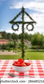 Bowl with strawberries with a out of focus background of a midsummer pole, a traditional sign of celebration of the upcoming summer. Strawberries have a strong connection to midsummer.