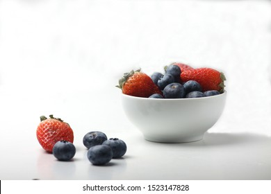 a bowl of strawberry and blueberry isolated on white background. Image contains copy space