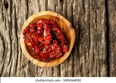 Bowl of sun dried tomatoes on wooden background, top view or flat lay. Minimal composition