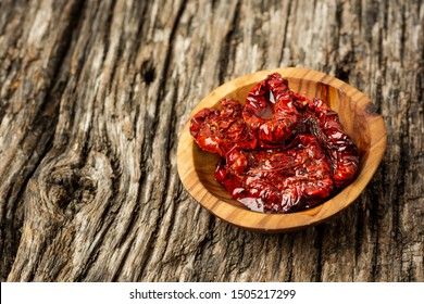 Bowl of sun dried tomatoes on wooden background, top view or flat lay. Minimal composition.