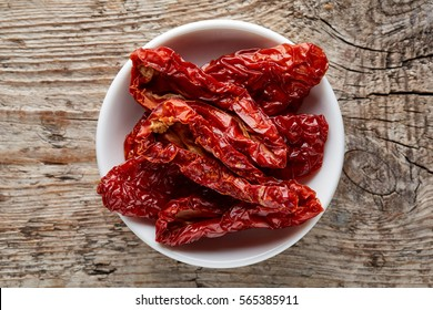 Bowl of sun dried tomatoes on wooden background, top view