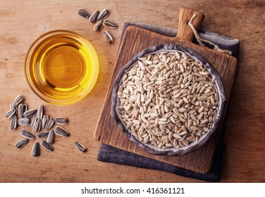Bowl of sunflower oil and sunflower seeds on wooden background. From top view