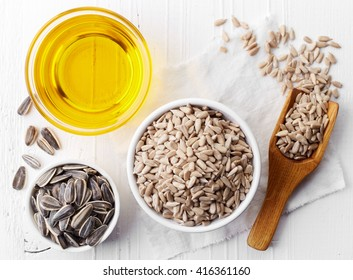Bowl of sunflower seeds and bowl of sunflower oil on white wooden background. From top view