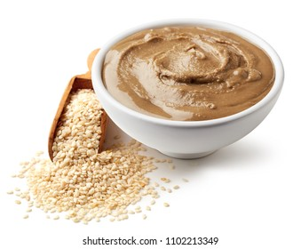 Bowl of tahini sauce and sesame seeds isolated on white background
