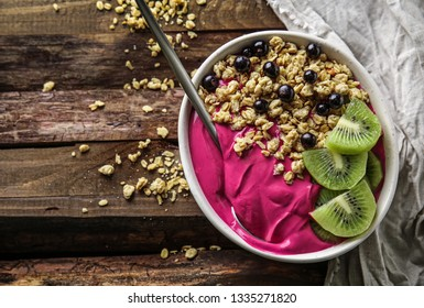 Bowl with tasty acai smoothie on wooden table