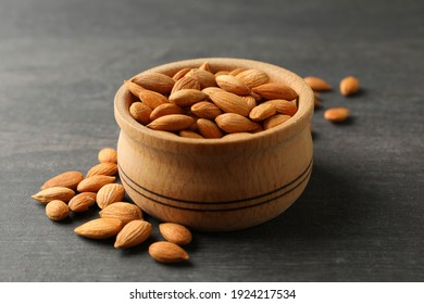 Bowl with tasty almond on gray wooden background