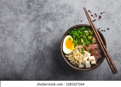 Bowl of tasty Asian noodle soup ramen with broth, tofu, pork, egg on grey rustic concrete background, space for text, close up, top view. Hot tasty Japanese ramen soup for dinner with copy space