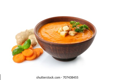Bowl with tasty carrot ginger soup on white background
