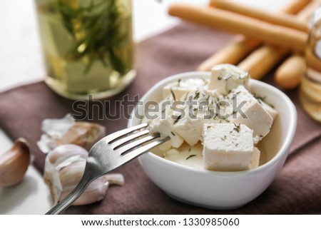Bowl with tasty feta cheese and garlic on table